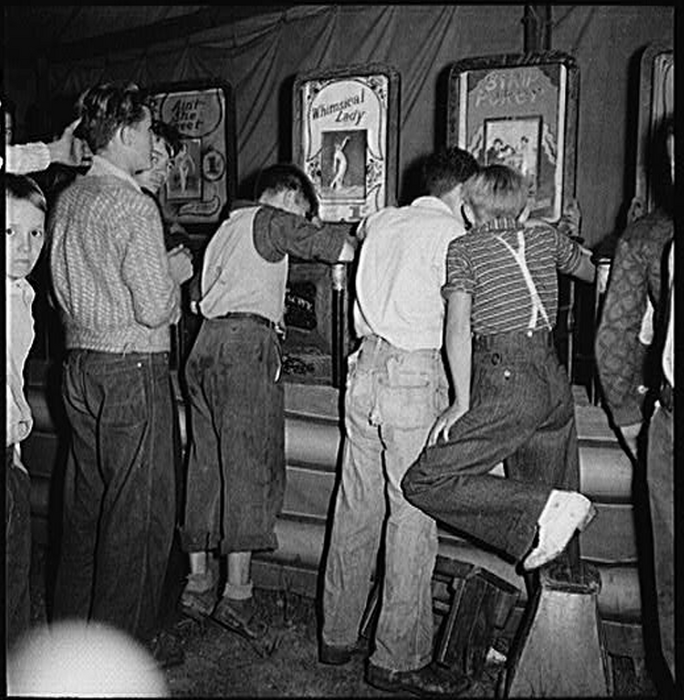 "Marion Post Wolcott's ""It's a dirty jip,"" say the mine workers' sons in the penny arcade at outdoor carnival. Granville, West Virginia, September 1938."