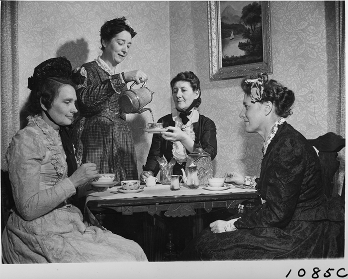 Women in period costume drinking tea