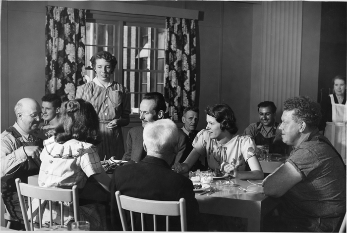 Norma Williamson (standing), student dietician from Willowdale ON, serves a full course chicken dinner to Claude Phillips (head electrician), Phyllis Walters (back to camera), clerical worker, Henry Wall, carpenter, Bill Kirkham, head carpenter, Doreen Robinson, runner and John Hall, restaurant designer. 60 people who were involved with the Balcony restaurant renovation in 1948 were treated to the first meal.
