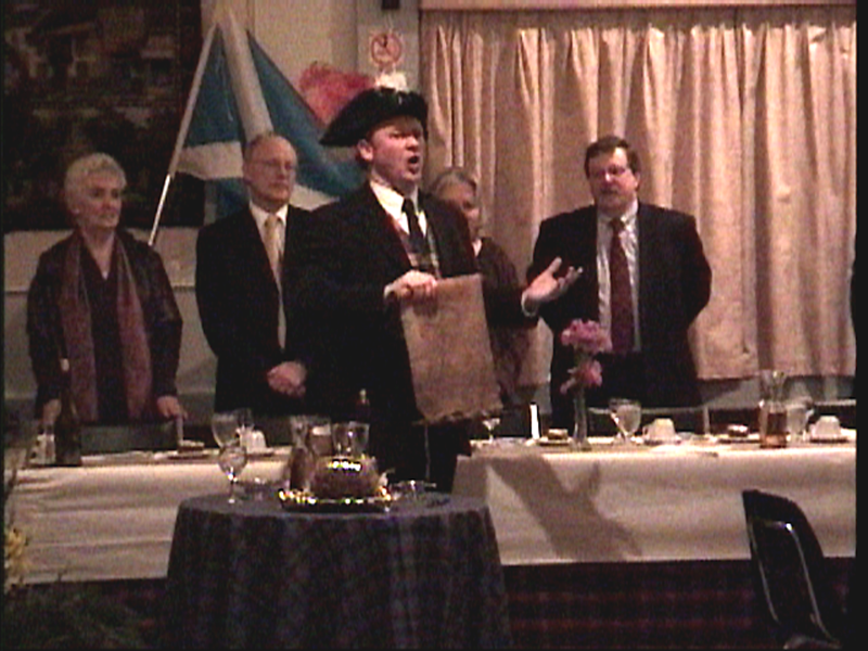 "Christopher Pickard ""addresses"" the haggis with the words of Burns's poem, with the hat and scroll from his role as town crier for the City of St. John's."