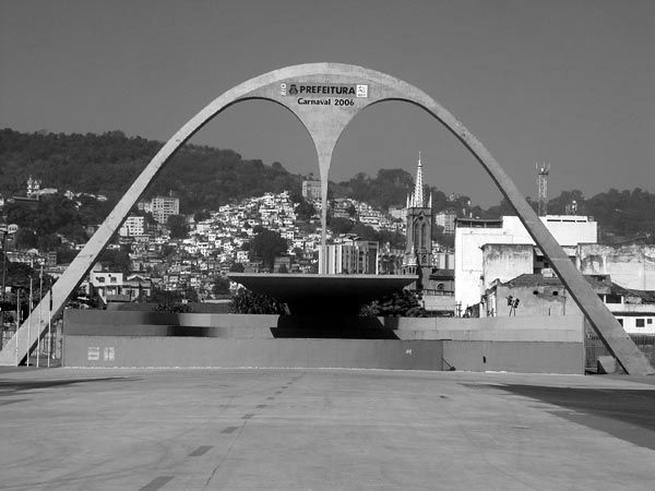 Band-shell on the Praça da Apoteose at south end of the Sambódromo (Oscar Niemeyer, 1984). A favela of Santa Teresa lines the hill slope in the background.