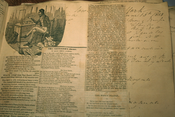 A page of the Loveland scrapbook showing an illustration of an editor at his desk and underlying ship's log